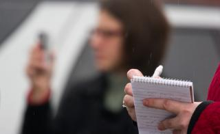 Woman in foreground holding a reporter's notebook