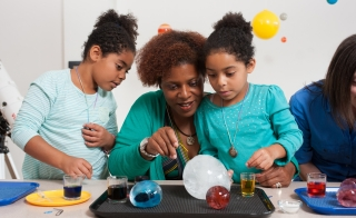 woman and children working on science experiment
