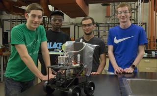Photo of Jayse Langdon, Jon Simiyu, Andrew Dopilka and Alex Cook as they work on their fuel-cell-powered car in preparation for the national American Institute of Chemical Engineers' Chem-E-Car competition this November.
