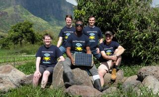 Five people sitting on rocks on farm in front of mountains with SolarSPELL unit