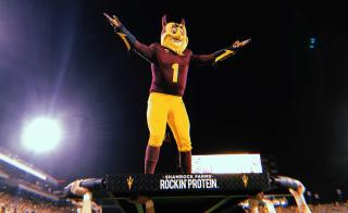 ASU mascot Sparky stands on a platform held by other students at a football game