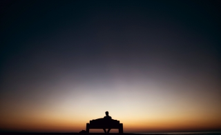 An image of a person sitting alone on a bench at sunset