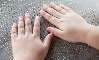 hands on a page of Braille