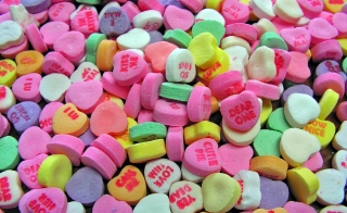 A pile of candy hearts with messages stamped on them.