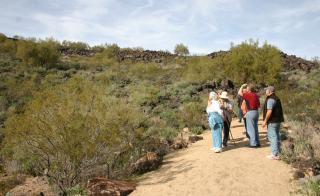photo of Deer Valley Petroglyph Preserve visitors looking at rock art