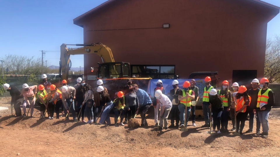 A line of ASU architecture students break ground on an outdoor classroom project