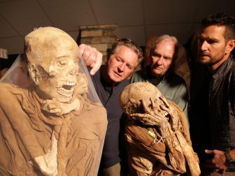 three men looking at two mummies