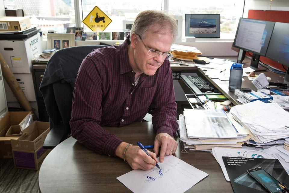 man diagramming on piece of paper