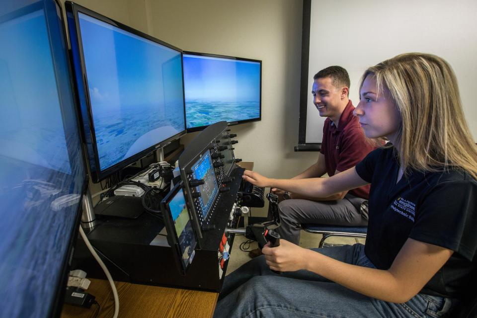 Aviation students practice with a flight simulator.