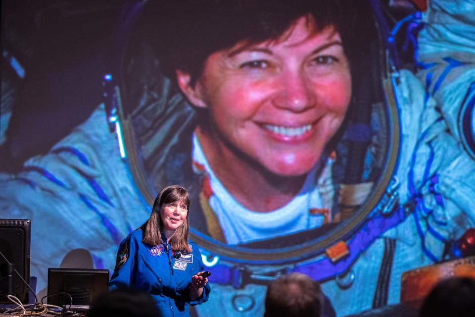 Global Explorer in Residence Cady Coleman delivers her inaugural lecture at ASU in front of a projection of a photo of her on a rocket