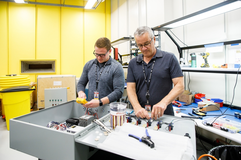Two men work with electrical equipment in a lab. The caption reads: Mechanical engineering student Alex Gardeck and engineer Steve Rednour work on an electrical control panel of the Compact X-ray Free Electron Laser.