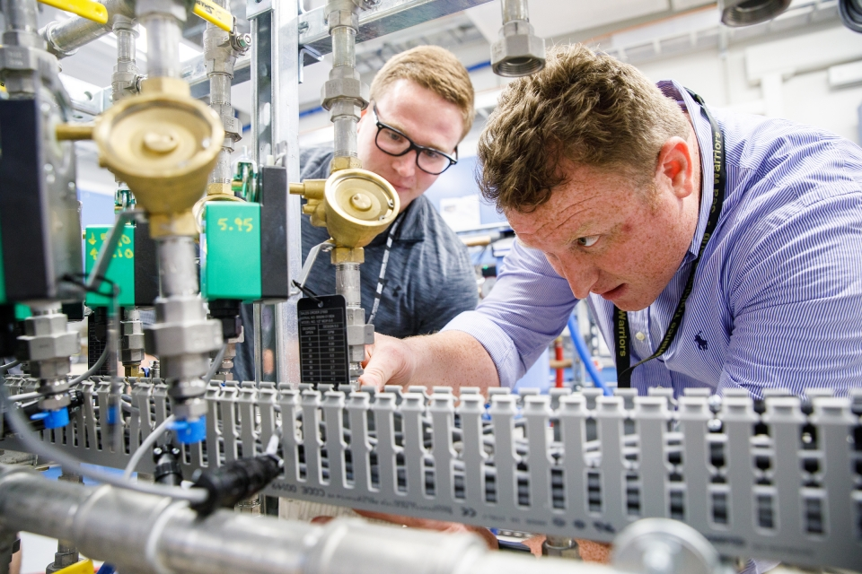 Two young men peer at an array of scientific components. The caption: Students Alex Gardeck and Brandon Cook examine the precision thermal trim unit water systems that controls the temperature of components in the radiography/fluoroscopy room.