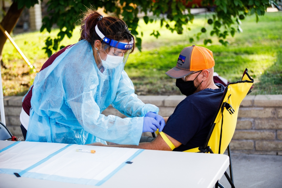 A woman in full personal protective gear indicates the site of blood draw on a man's arm.
