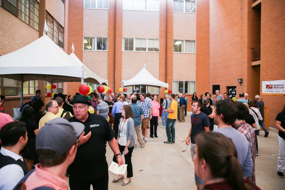 People gather in a brick courtyard for a celebration