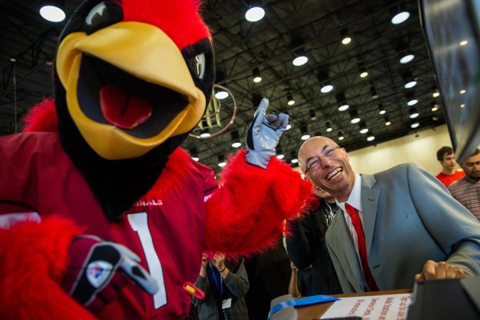 Bird mascot and well dressed man at a treadmill desk