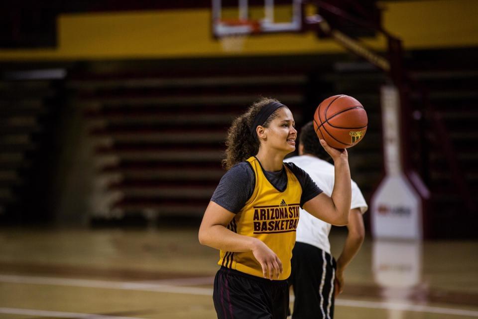 A woman playing basketball.