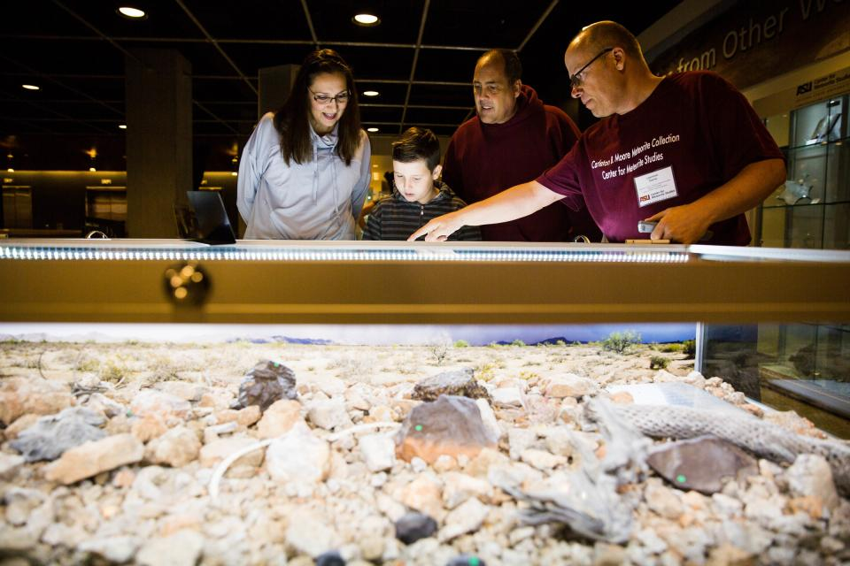 A family looks at a meteorite display.