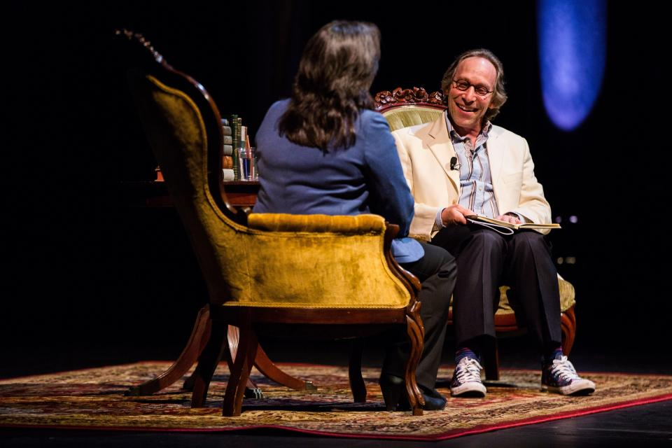 A man and a woman sit in easy chairs on a stage discussing science writing.