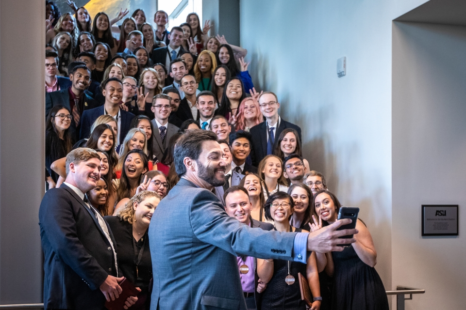 Dean Jonathan Koppell takes a group selfie in front of a staircase packed with Next Generation Service Corps students