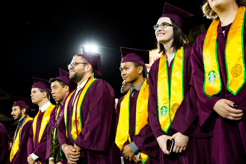 A row of graduates listen to the commencement ceremony in May 2019