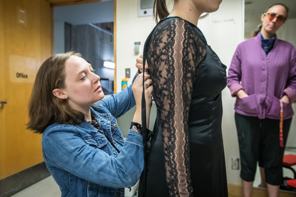 women kneeling to tailor dress worn by other woman