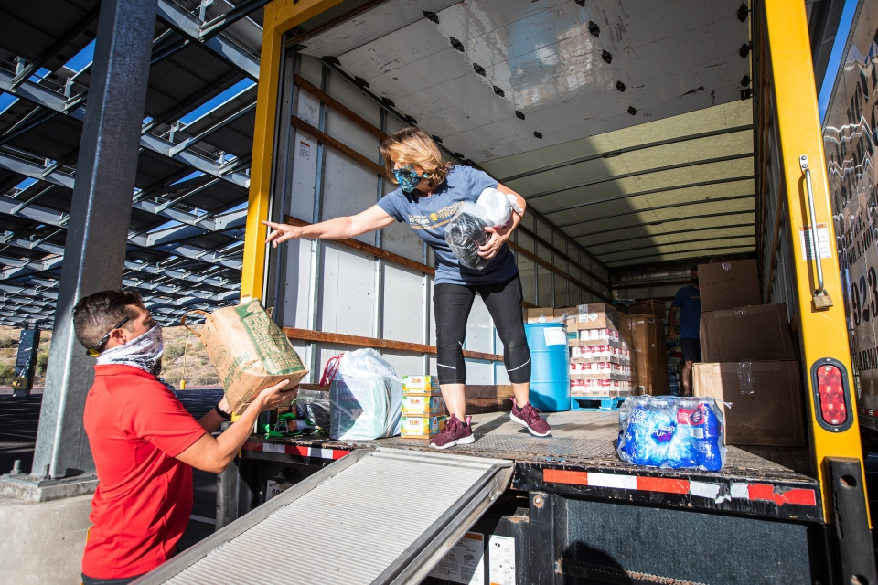 woman standing in a moving truck bed as a man helps load