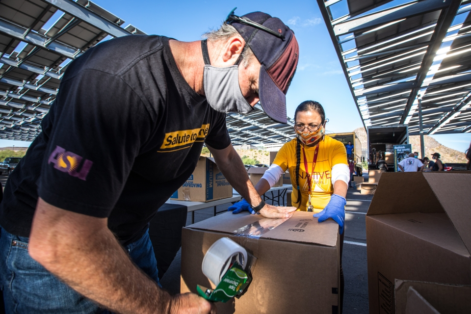 Volunteers tape up boxes of donations