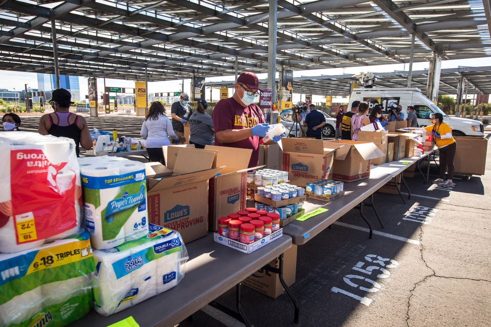 man standing at a long line of donation laden tables
