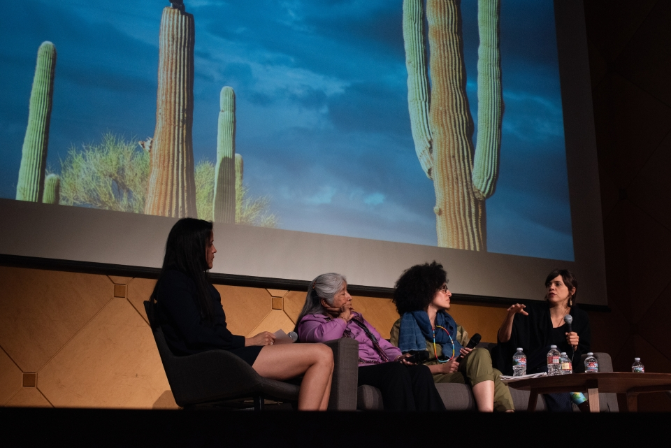 four women sitting and talking on a stage with a photo of cacti in the background
