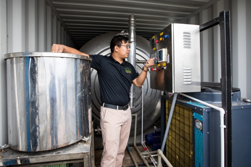 Zhihao Chen, inside the digester container, talks about the vertical farming system