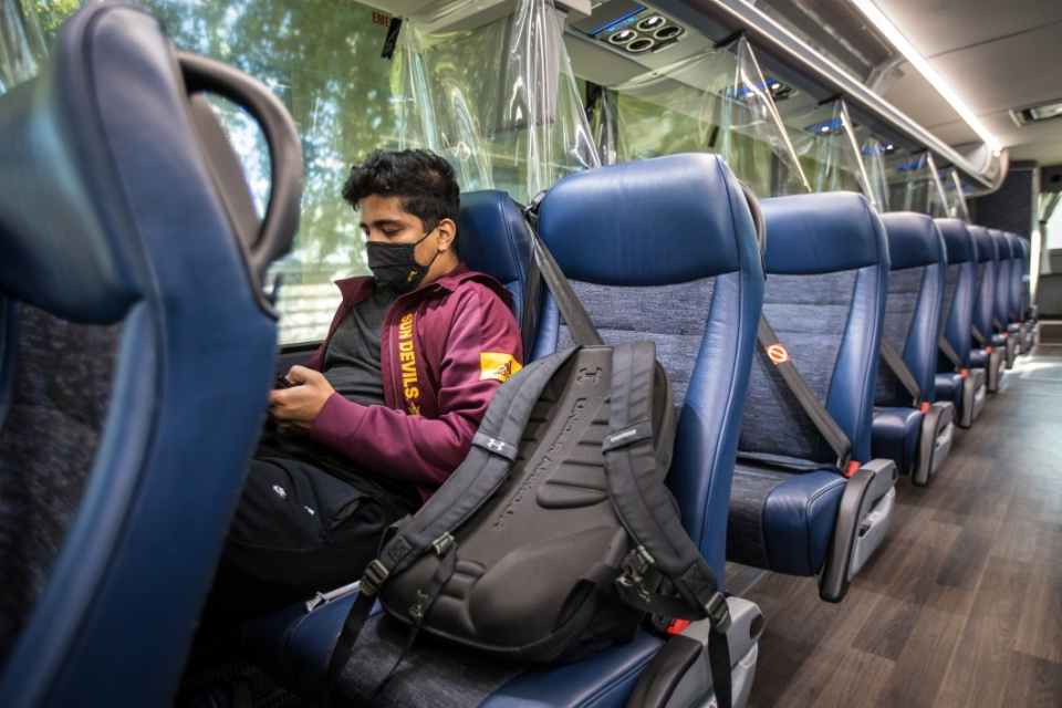 A student sits on an ASU shuttle with COVID partitions between each row