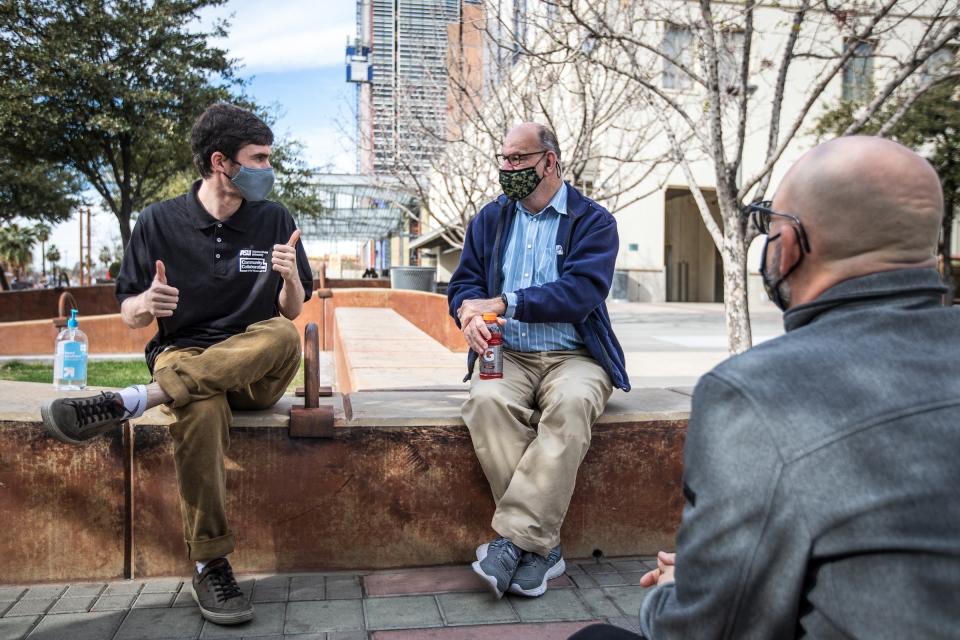 three men talking outside wearing masks