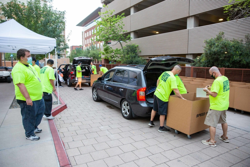 movers unpacking stuff into boxes from cars