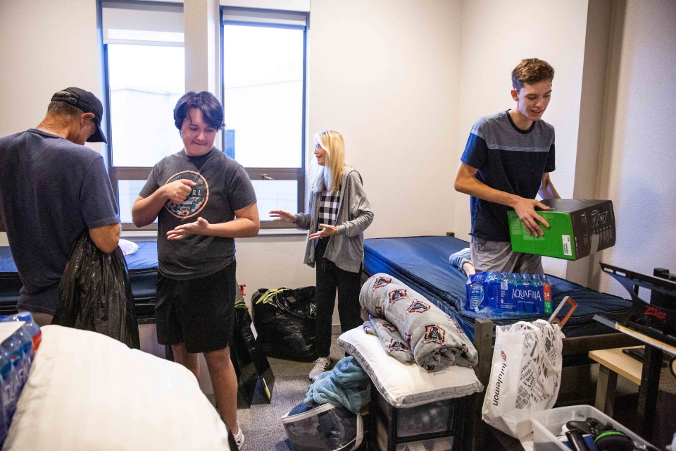students and family unpack in dorm room