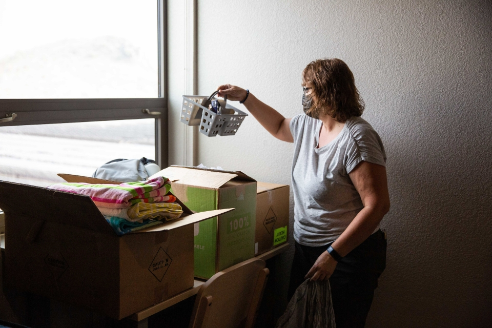 woman unpacking items in dorm room