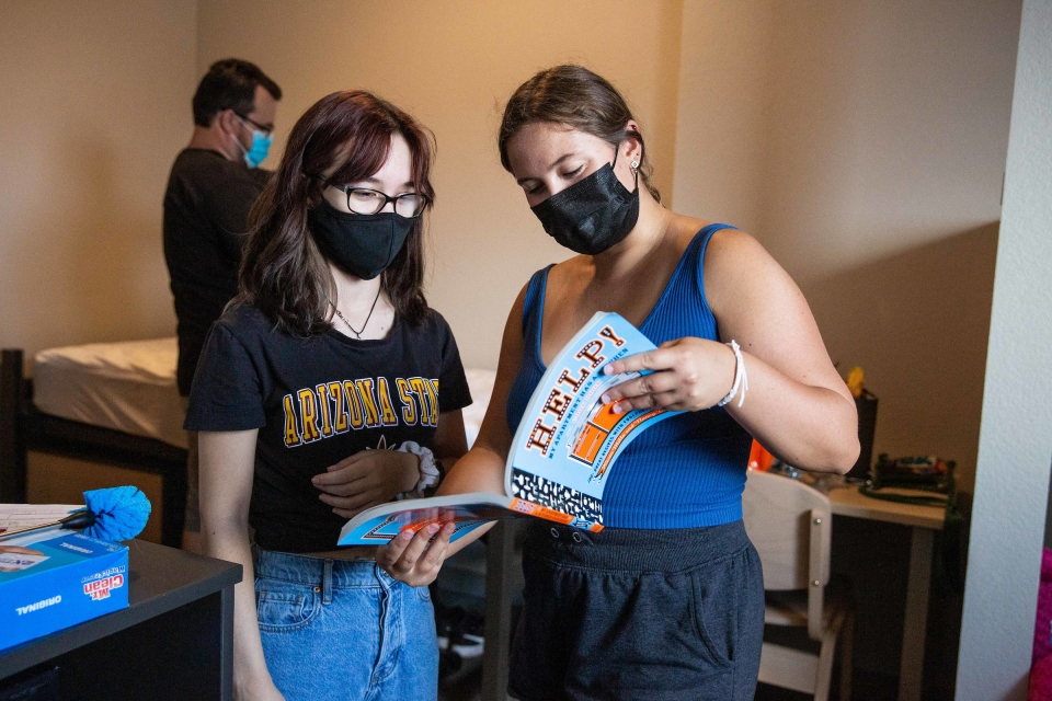 two students looking at cookbook
