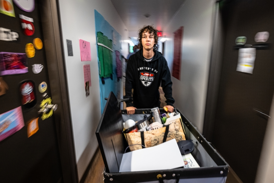 man pushing container with move-in supplies to room