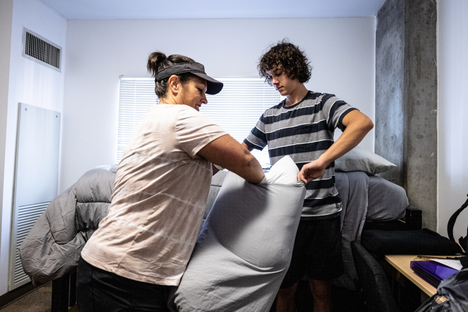 mother and son making dorm room bed