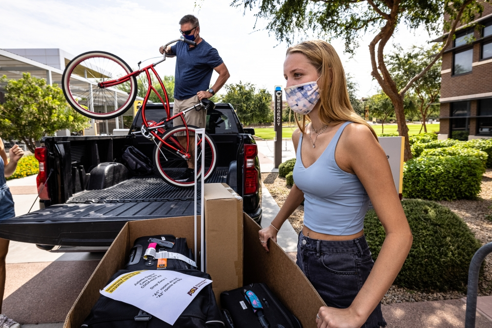 dad helping daughter unload bicycle from car