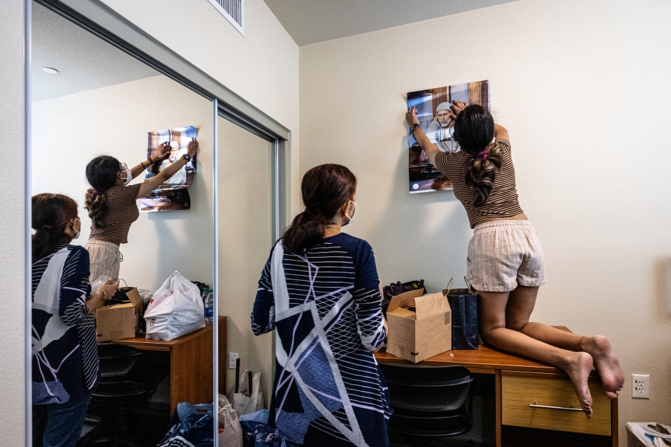 student hanging poster on wall in dorm room