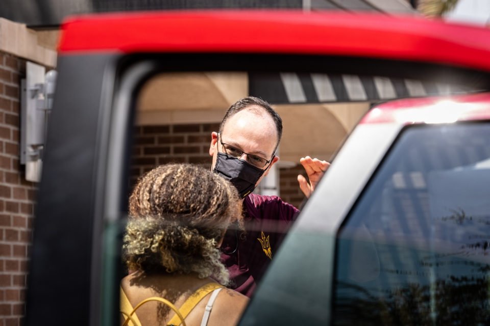 ASU dean talking to student by cars during move-in
