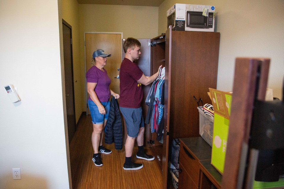 mom and student unpacking dorm room