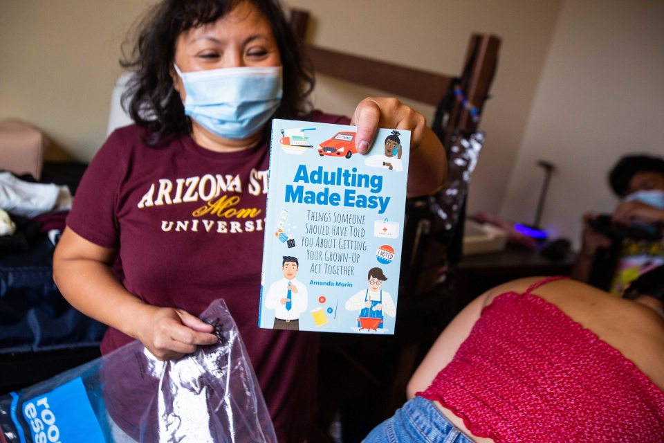 """woman holding a book titled """"Adulting Made Easy"""""""