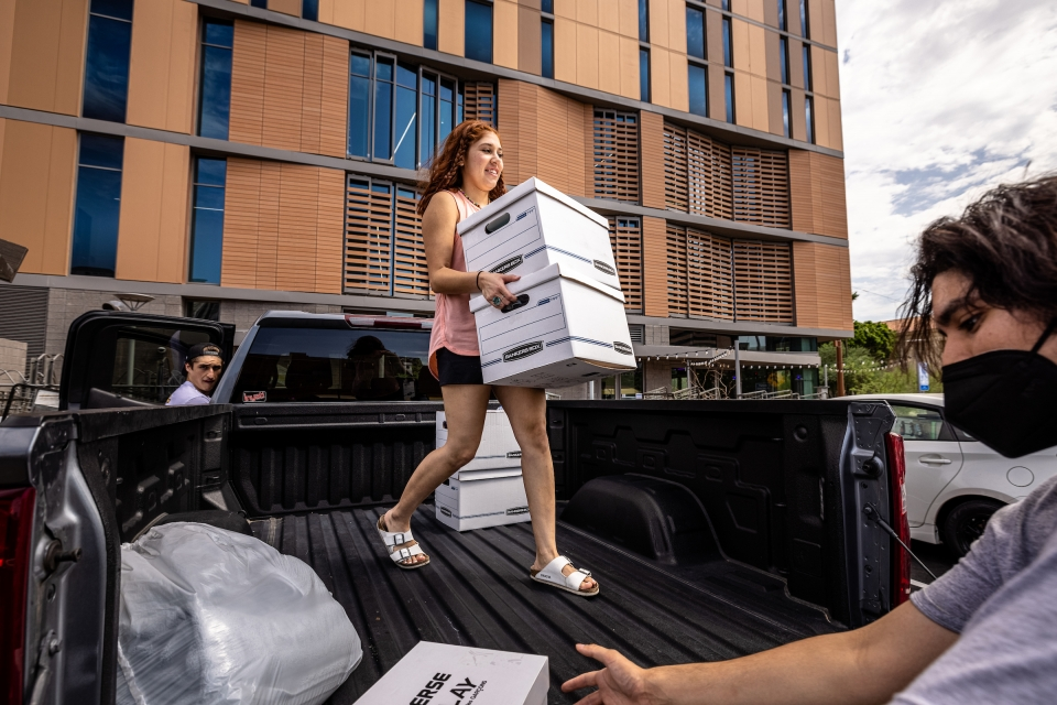 student carrying boxes off truck bed