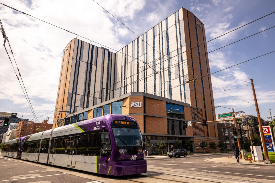 A light rail train crosses the street in front of a high-rise dorm