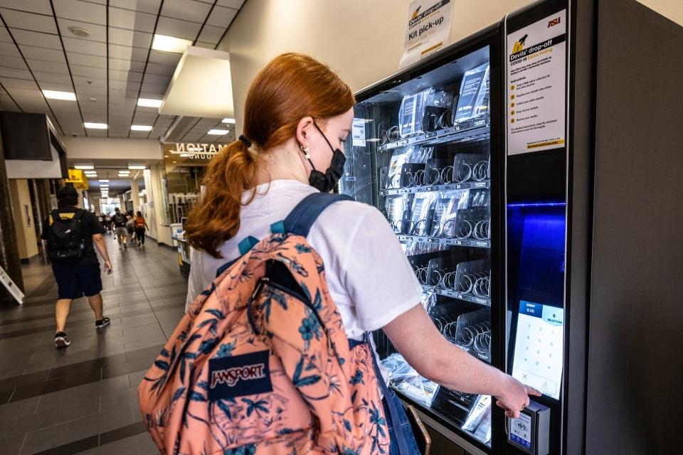 woman works a vending machine