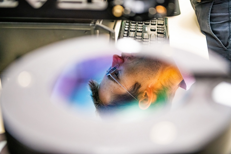 A man's face is seen reflected in a computer chip