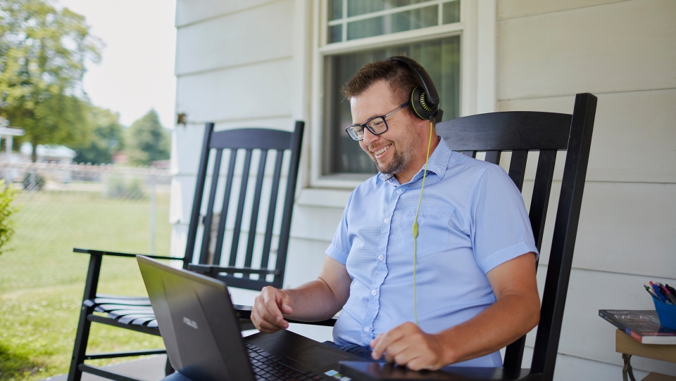 A man sitting in a rocking chair on a porch works on a laptop while wearing headphones