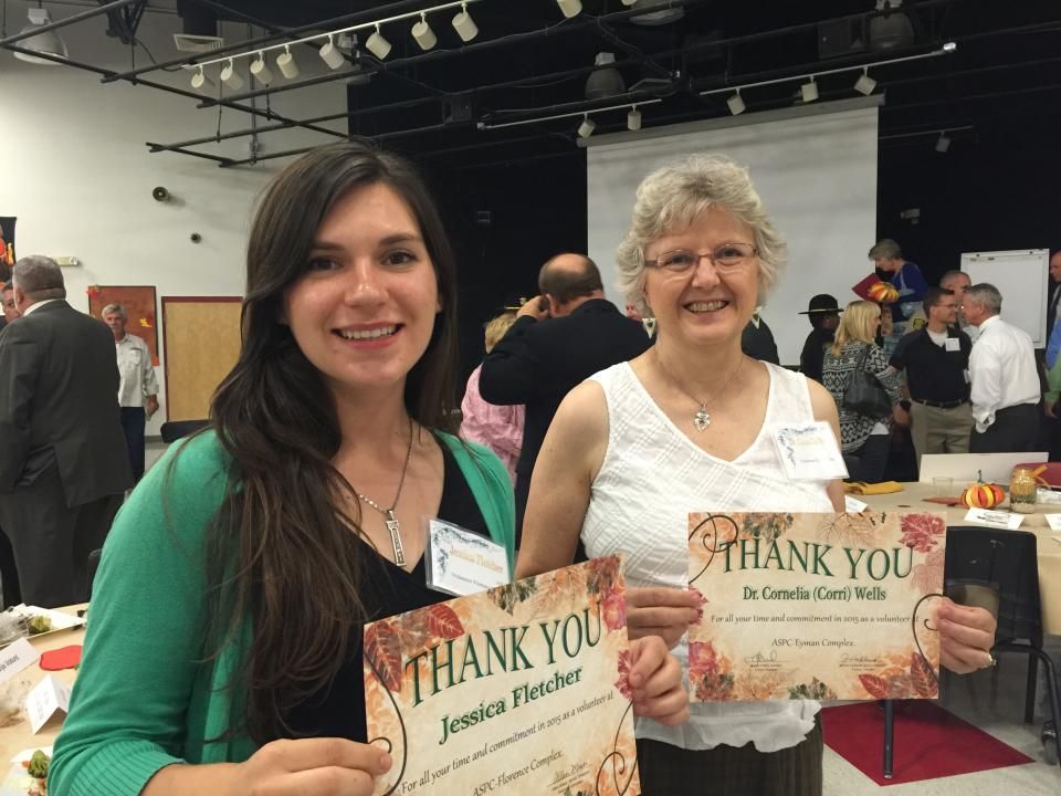 Two women hold certificates of appreciation.