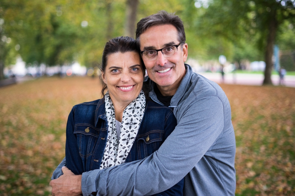 a woman and a man embrace and smile at the camera with a fall foliage scene in the background